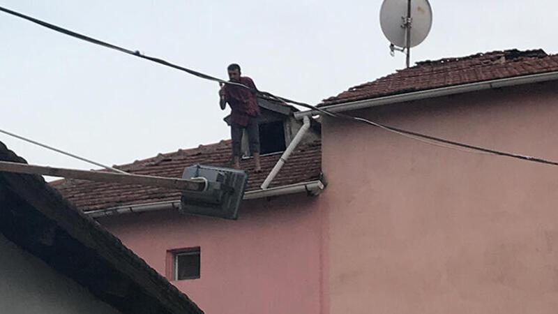 Ailesini göremediği için baltayla çatıya çıkan adam aşağı düştü